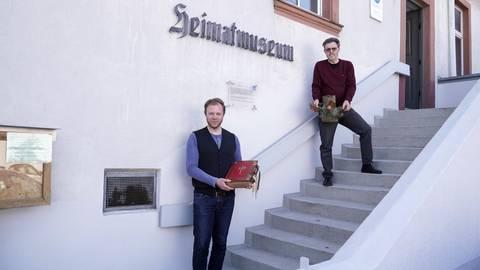 Der evangelische Pfarrer Nils Bührmann und Diakon Peter Schreiber (hinten) zeigen zwei Exponate, die in der Ausstellung im Bibel- und Heimatmuseum zu sehen sind. Foto: pp/Boris Korpak
