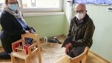 Kitaleiterin Bettina Köhler und Ortsbürgermeister Werner Kalbfuß zeigen den Schaden, der lange unterm Boden verborgen lag.
