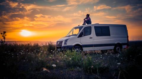 Lili Oberle sitzt auf ihrem Camper und genießt den Sonnenuntergang. Foto: Lili Oberle