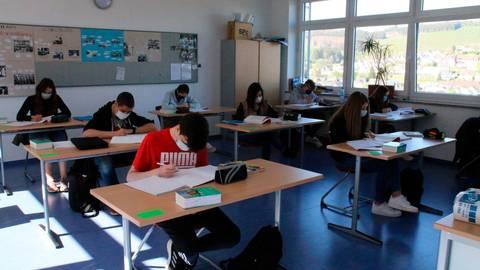 Es geht wieder los: Realschüler einer halbierten Klasse  der Holderbergschule bereiten sich einzeln sitzend und mit Mundschutz auf die Prüfungen vor.  Foto: Frank Rademacher