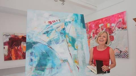 Zeigt den Weg von der Idee bis zum fertigen Bild: Renate Corell mit ihrem Skizzenbuch vor einem ihrer Werke im Atelier. Foto: photoagenten/Axel Schmitz