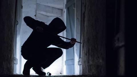 Ein Einbrecher steigt in ein Haus ein. Symbolfoto: dpa