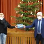 """Martin Hanika überreicht Anja Asmussen und allen übrigen Anwesenden eine Lebkuchendose mit dem Motiv """"Dorfidylle"""". Foto: Rieger"""