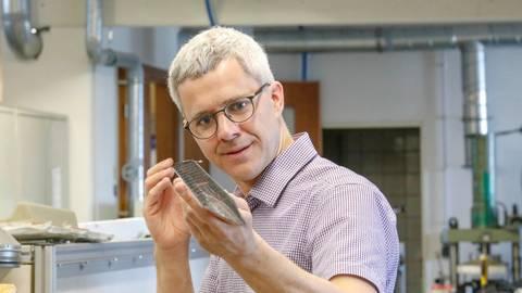 Ein Stück Handarbeit für den Teilchenbeschleuniger: Christoph Möller und eines der Bauteile aus seiner Werkstatt. Foto: Torsten Boor