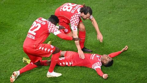 Danny da Costa und Adam Szalai feiern Siegtorschütze Leandro Barreiro (von links). Foto: dpa