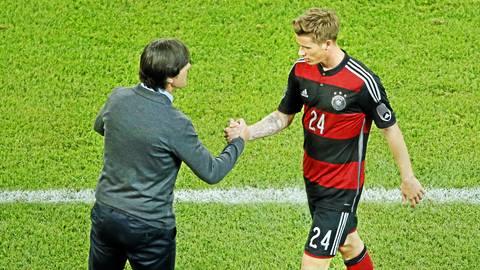 Der ehemalige Nationalspieler Erik Durm im Trikot der deutschen Nationalmannschaft mit Bundestrainer Joachim Löw.  Foto: dpa
