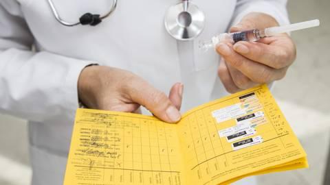 Ein Arzt hält einen Impfausweis und eine Spritze in den Händen. Foto: dpa