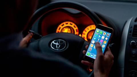 Streng verboten: Ein Fahrzeug steuern und dabei gleichzeitig sein Handy benutzen - das kann teuer werden, wenn einen die Polizei dabei erwischt. Symbolfoto: Monika Skolimowska/dpa
