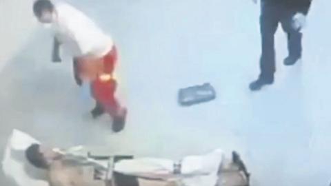 Auf dem Video ist zu sehen, wie ein Sanitäter zum Schlag gegen den Mann ausholt. Polizisten sehen zu. Screenshot: VRM/bild.de