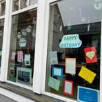 Die Karten- und Bilderausstellung in den Fenstern des Eingangsbereichs gibt Einblicke in die Projekte. Foto:  Herdejost