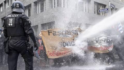 """Die Polizei setzt einen Wasserwerfer auf die Gegner der """"Querdenken""""-Demonstration in der Frankfurter Innenstadt ein.  Foto: dpa"""