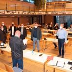 Christian Harms, Vorsitzender der Gemeindevertretung, vereidigt die ehrenamtlichen Beigeordneten des neuen Gemeindevorstands Weilmünster, Bürgermeister Mario Koschel (rechts) überreicht anschließend die Ernennungsurkunden. Foto: Dorothee Henche