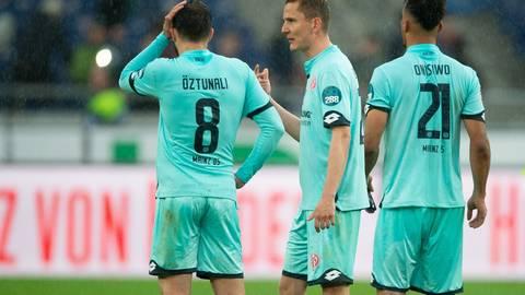 Levin Öztunali, Niko Bungert und Karim Onisiwo (l. nach r.) unterhalten sich nach dem Spielende. Foto: dpa