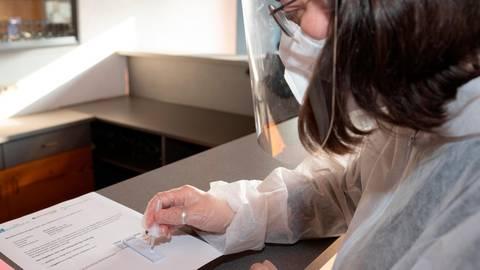 Die pharmazeutisch-technische Assistentin Paula Bäcker träufelt die Lösung auf den Teststreifen. Nach etwa 15 Minuten steht das Ergebnis fest.  Foto: Mark Adel