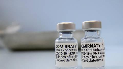 Fläschchen mit dem Biontech-Impfstoff Comirnaty stehen auf einer Theke in einer Hausarztpraxis. Foto: dpa/Paul Zinken