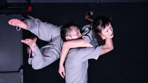 """Sie tragen schwer an ihrer Liebe: Kuan-Ying Su schultert Yi-Wei Lo im Tanzstück """"Kick the Bucket"""". Foto: Susanne Reichardt"""