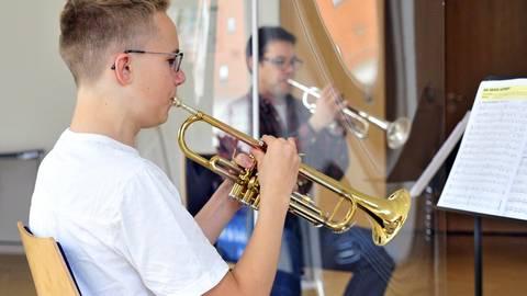 Musiklehrer Björn Colditz (rechts) und sein Trompeten-Schüler Johannes Joneleit halten Abstand und sind durch eine Plexiglasscheibe voneinander getrennt. Foto: Thomas Schmidt