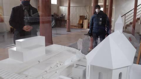 Ein Modell in der Kirche zeigt anschaulich die künftige Gestaltung, die Pfarrer Carsten Stein (links) und Architekt Arno Klinkenberg erläutern. Direkt links neben der Kirche der entstehende Anbau, ganz links die bestehende Friedhofshalle. Foto: Bernhard Bergmann/Dekanat