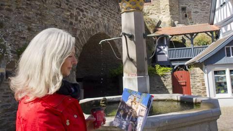 """Patricia Bastian-Geib erkundet mit der Neuauflage des """"Stadtrundgangs"""" Idstein. Hier steht sie am Löwenbrunnen auf dem König-Adolf-Platz. Foto: Mallmann/AMP"""