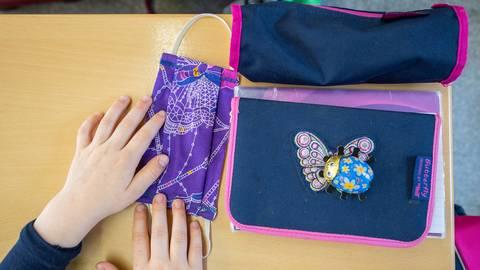 Eine Schülerin hat eine Stoffmaske auf ihren Tisch neben ihre Schul-Utensilien gelegt. Symbolfoto: dpa