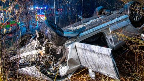 Der Mercedes schleuderte gegen einen vorausfahrenden Nissan und beschädigte diesen, geriet im Anschluss nach rechts von der Fahrbahn ab, überschlug sich und blieb auf dem Dach in einem Waldstück liegen. Foto: Fuldamedia