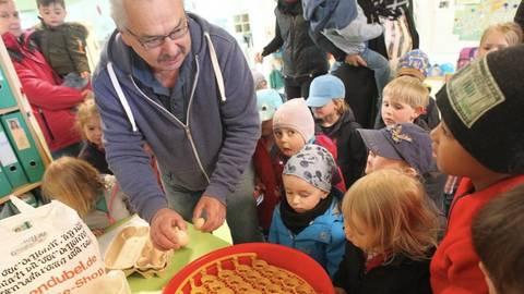 Geflügelzüchter Reinhard Wejwoda zeigt den Kindern die Eier, die er in den Heizapparat legt.                                            Foto: hbz/Jörg Henkel   Foto: hbz/Jörg Henkel