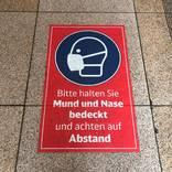 An Bahnhöfen wird auf Schildern auf das Tragen von Masken und die Abstandregeln hingewiesen. Foto: Maximilian Brock