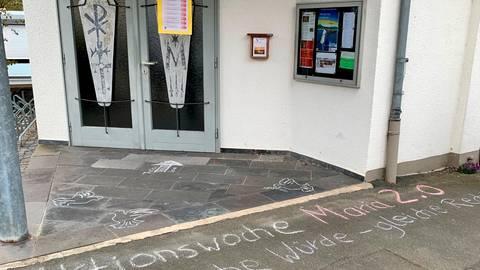 Die Akteure der Reformbewegung 2.0 haben das Motto ihrer Aktion vor der Kirchentür mit Kreide notiert.  Foto: Christian Walendsius