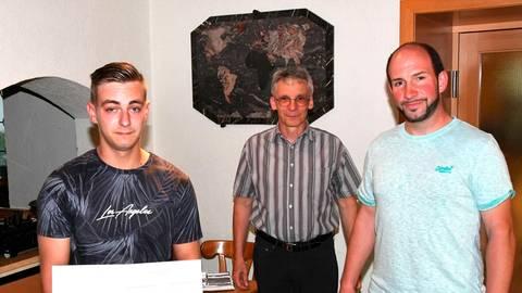 Obermeister Christian Arkularius (r.) und Stefan Laßmann überreichen Tom Pascal Pietzner (l.) die Urkunde. Foto: Klaus-Dieter Häring