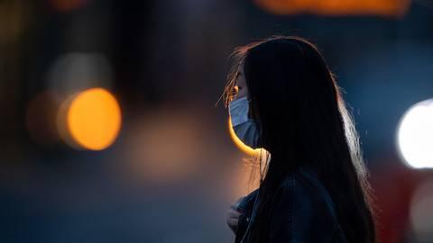 Eine Frau mit Mund- und Nasenschutz wartet an einer Ampel.    Foto: dpa