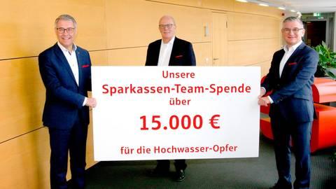 Roman Kubler, Thomas Falke und Frank Dehnke (v.l.) präsentieren für den Vorstand der Sparkasse Oberhessen den symbolischen Spendenscheck für die vom Hochwasser Geschädigten. Foto: Zimdars