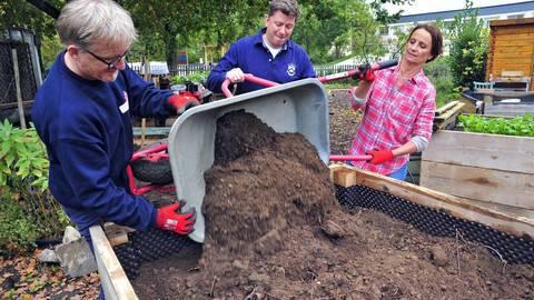 """Mit vereinten Kräften schütten Matthias Reinig (Mitte) und seine Kollegen das Hochbeet im Garten des Mehrgenerationenhauses auf. Ein neuer Zaun stand ebenfalls auf der """"to-do""""-Liste. Foto: Thomas Schmidt"""