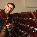 """Heiko Bamberger am Rüttelpunkt. Jeden Tag muss die Sektflasche um eine Vierteldrehung bewegt werden, damit sich die Hefe im Flaschenhals sammelt. So hat er es auch mit jenem Schaumwein gemacht, der jetzt als """"Sekt des Jahres"""" ausgezeichnet wurde. Foto: Wolfgang Bartels"""