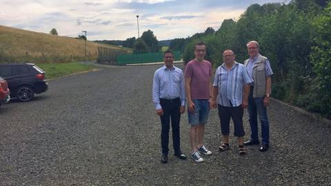 Die SPD-Fraktionsmitglieder Patrick Krug, Klaus Weitzel und Walter Theis machen sich gemeinsam mit dem SPD-Landtagsdirektkandidaten Swen Bastian ein Bild des sanierten Parkplatzes. Foto: Krug