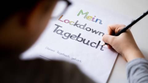 Ein Grundschüler malt an einem Tisch im Wohnzimmer die Buchstaben eines Lockdown Tagebuchs aus. Um die Frage, ob die Schulen während der Corona-Krise weiter geschlossen bleiben sollten, ist eine Debatte entbrannt. Symbolfoto: dpa