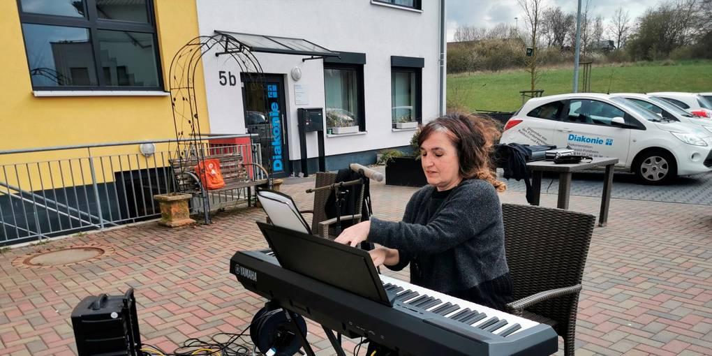 Ungewöhnlicher Konzert-Ort: Gitty Feriduni spielt auf dem E-Piano, die Bewohner singen auf den Balkonen mit. Foto: Lanzet-Hallen