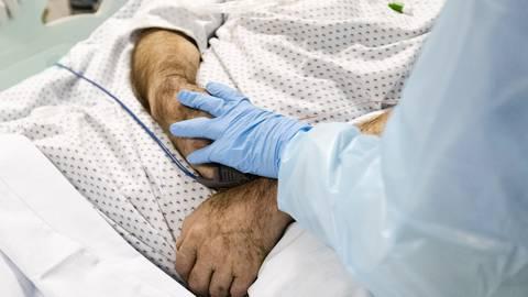Eine Krankenschwester berührt die Hand eines am Coronavirus erkrankten Patienten. Foto: dpa