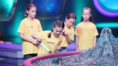 """Loretta (vorn) kämpft bei """"Bellz"""" um den Sieg. Ziel des Spiels ist es, so viele magnetische Bellz-Kugeln der am Anfang des Spiels gewählten Farbe einzusammeln. Dabei müssen die Teams aufpassen, dass sie wirklich nur die gewählte Farbe erwischen, ansonsten ist der jeweilige Durchgang verloren. Wer am Ende die meisten Bellz-Kugeln seiner gewählten Farbe eingesammelt hat, gewinnt das Spiel. Im Hintergrund drücken Victoria, Mila und Mira (von links) ihrer Teamkameradin die Daumen. Foto: RTL Disney Fernsehen GmbH & Co. KG"""