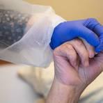 Eine Altenpflegerin in Schutzausrüstung hält die Hand eines Heim-Bewohners. Foto: dpa