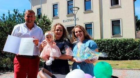 Bürgermeister Mario Koschel zeigt die Urkunde, die Medihade Perteshi (Mitte) für die Ehrenpatenschaft ihrer jüngsten Tochter Luana erhält, mit dabei die älteste Tochter Leonora.  Foto: Dorothee Henche