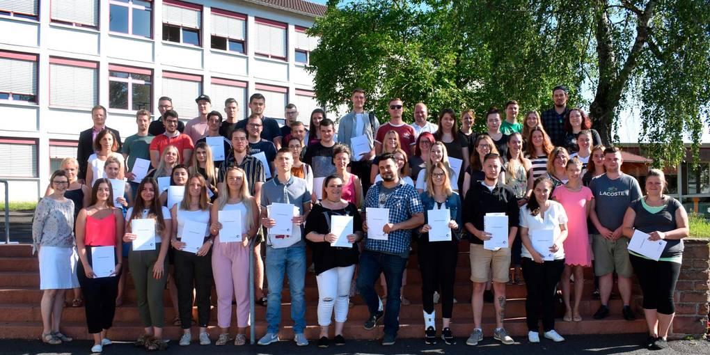 Drei Jahre lang haben die jungen Leute in Betrieben der Region gelernt und sind in der Beruflichen Schule in Büdingen ausgebildet worden. Stolz halten sie jetzt ihre Abschlusszeugnisse hoch. Foto: Eichenauer