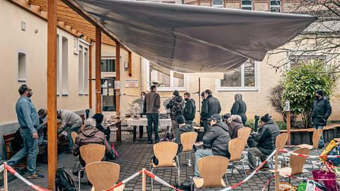 Im Hinterhof der Teestube der Diakonie in Wiesbaden wird täglich Essen ausgegeben. Am 13. und 14. Mai können sich dort die Wiesbadener Obdachlosen gegen Corona impfen lassen, wie Leiter Matthias Röhrig (links, stehend) berichtet. Foto: Andreas Baumbach