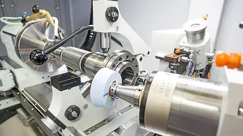 Eine Hochpräziszionsschleifmaschine bei der Arbeit: Das Werkstück aus Metall wird nach Kundenwunsch bearbeitet.   Foto: Overbeck