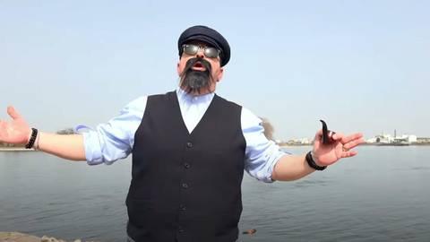 """Für das lustige Musikvideo hat sich Woody Feldmann als  Fährmann verkleidet. Gedreht wurde unter anderem am Niersteiner Rheinufer und auf der Fähre """"Helene"""". Foto: Woody Feldmann YouTube"""