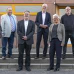 Dem Gemeindevorstand gehören (von links) Klaus Unger (CDU), Ulrich Selle (SPD), Bürgermeister Thomas Raschel (CDU), Erster Beigeordnete Ursula Kraft (CDU), Thomas Hornung (Grüne) und Klaus Senfft (SPD) an. In der Mitte steht Parlamentschef Michael Barth (CDU). Foto: Vollformat/Robert Heiler