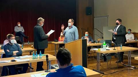 Der alte und neue Leuner Stadtverordnetenvorsteher Jürgen Ambrosius (links stehend) vereidigt Ralf Schweitzer als ehrenamtlichen Stadtrat, rechts im Bild stehend Bürgermeister Björn Hartmann.  Foto: Verena Napiontek