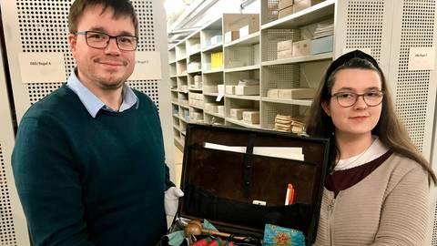 Christian Pöpken und Laura Rohrbeck zeigen einen Ausschnitt des Bestandes der Gießener Freimaurer. Foto: Scholz