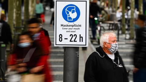 Ein Mann steht mit Maske neben einem Hinweisschild ·Maskenpflicht· auf der Einkaufsstraße Zeil in Frankfurt. Archivfoto: dpa