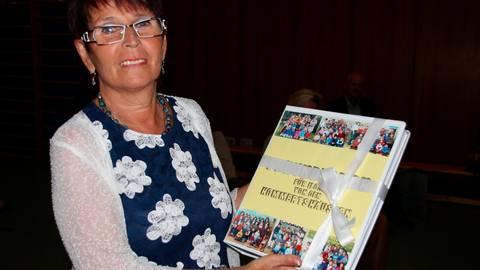 Von den Eltern, die sie teilweise früher selbst als Kinder betreut hat, erhielt Ilona Solms ein Freundschafts- und Erinnerungsbuch, in dem sie im Ruhestand schmökern kann. Foto: Sascha Valentin