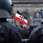 Neonazis schwenken bei einer Demo eine Fahne hinter einer Polizeikette.  Archivfoto: dpa/Jan Woitas